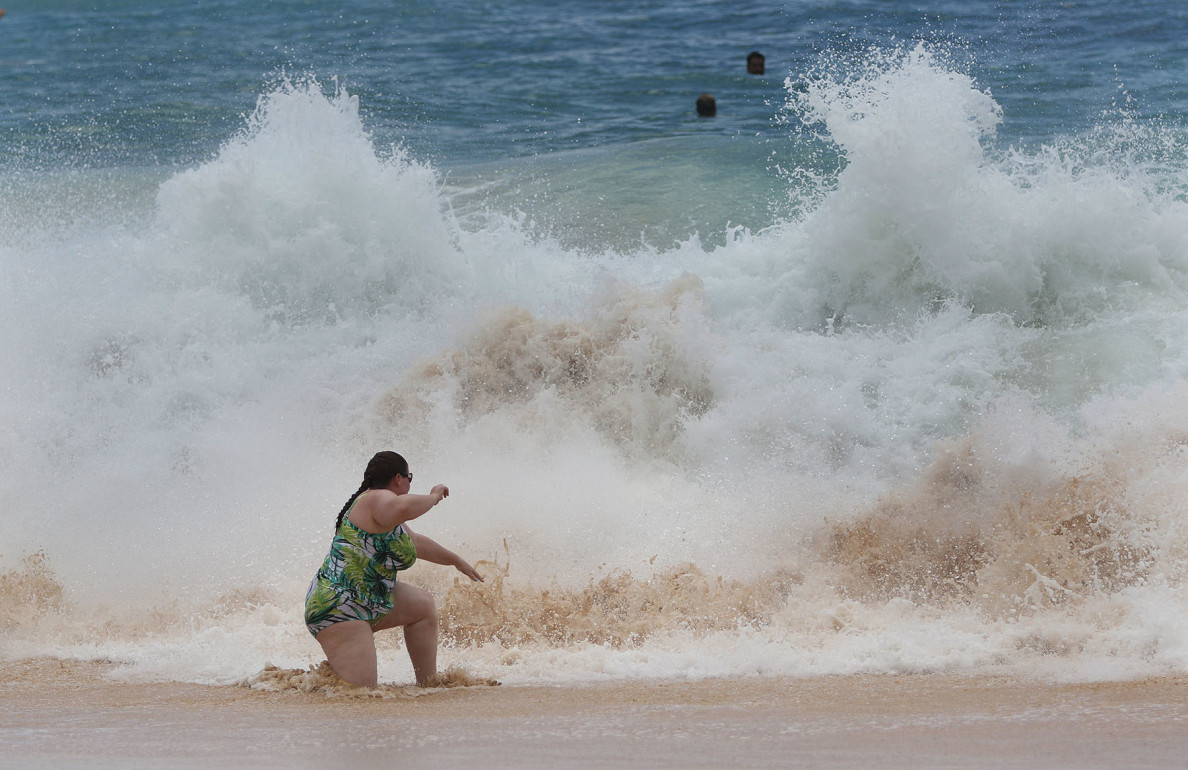 A woman struggles in the pounding waves at Sandy Beach where the shore break is one of the most treacherous in the state.