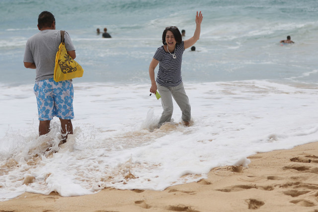 Visitors laugh and enjoy an errant shore break wave while not paying attention to the wave sets at Sandy Beach.