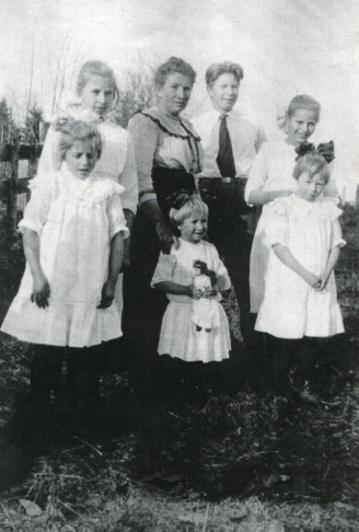 A family photo includes Gladys as a little girl holding a doll with her mother and older siblings.