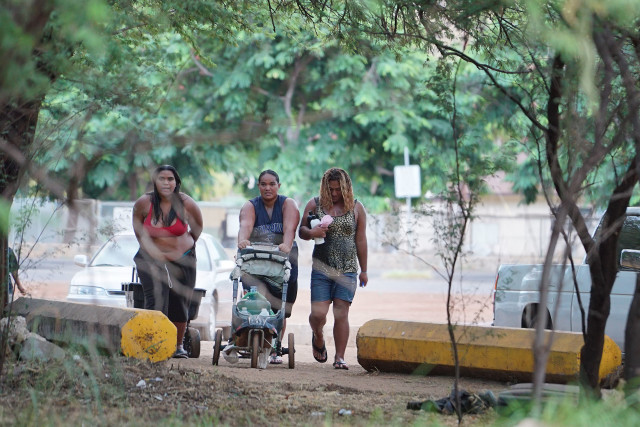 Queenie, left, Tamra and Adam return to the camp after using hoses in the boat harbor to shower.