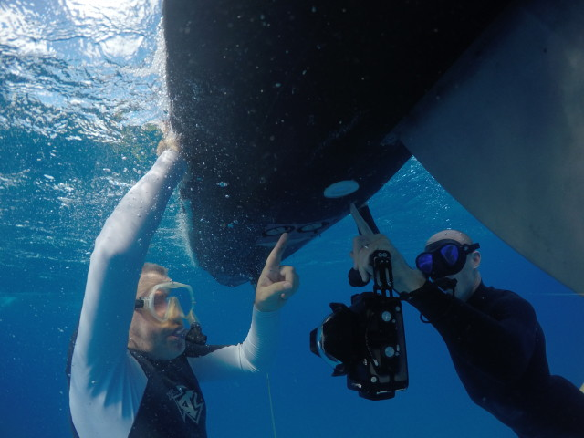 Frazer McGilvray of Malama Maunalua, left, and Derek Cuny of Liquid Robotics point at the downward facing camera on the bottom of the Wave Glider, Thursday, in Maunalua Bay.
