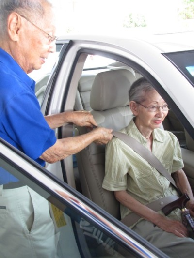 Poject Dana volunteer Harold Kuwahara helps Ann Shiroma, 91, buckle up before he drives her to her medical appointments and grocery shopping.