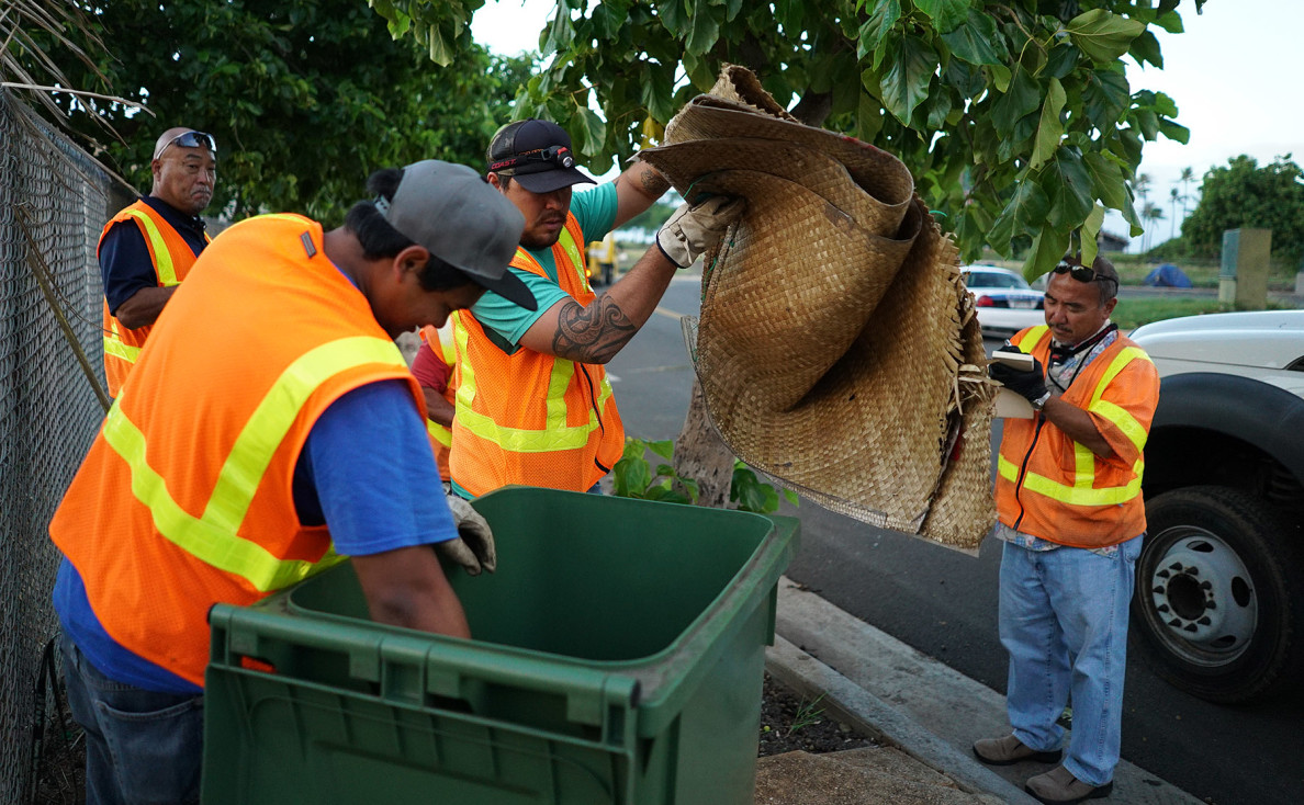 The city's maintenance crew stores a backpack, woven mat and other personal items found on Ohe Street during a Tuesday sweep in Kakaako.