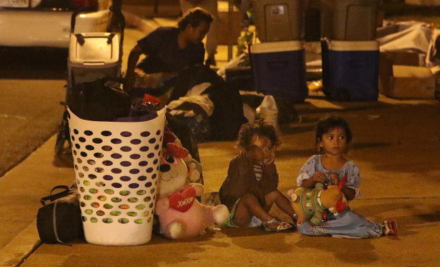 A contractor hired to handle trash during a homeless sweep in Kakaako last December picks up cardboard, coconuts and other trash just after 5 a.m. as three little girls wait patiently for what's next.