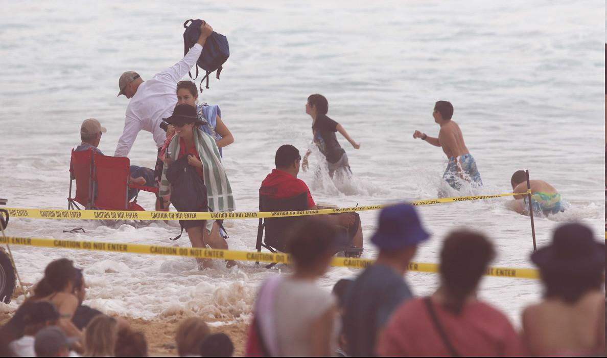 Ehukai Beach watch surf contest as an errant surge heads up the shoreline sending people scrambling. Oahu. Surf. 9 dec 2015. photograph Cory Lum/Civil Beat