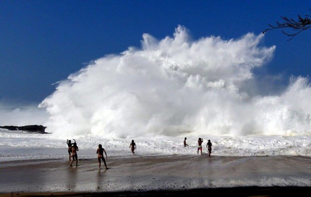 Beachgoers play in massive surf Wednesday at Lumahai Beach.