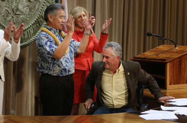 Avery Chumbley completes the signing of the hospital documents as Mary Ann Barnes, Hawaii president of Kaiser Foundation Hospitals and Health Plan, cheers along with left Gov. David Ige.
