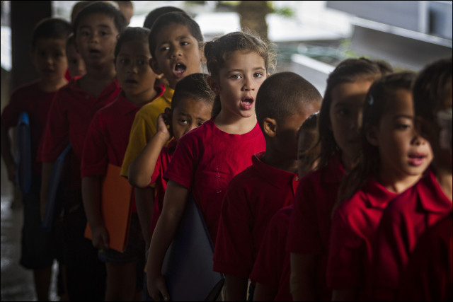 Students sing during start of day protocol at the  Nawahiokalani'opu'u Hawaiian Immersion School in Keaau, Hawaii.