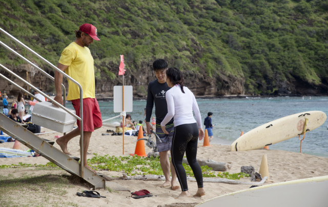 Lifeguard Josh Guerra helps a visitor who cut his foot at Hanauma Bay.