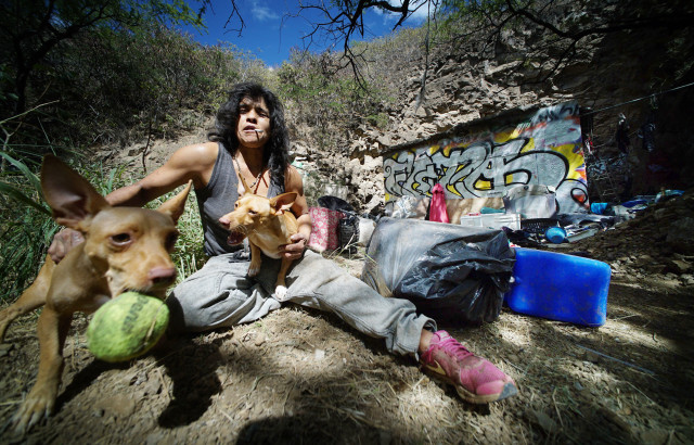 Diamond Head slopes resident Bernadette plays with her dogs named Piranha1 and Piranha2 along the slopes of Diamond Head.