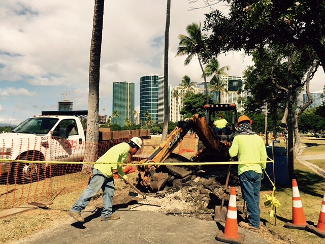 Workers dig up parts of the jogging pathway at Ala Moana Beach Park to be repaved with new asphalt and covered with sealant and painted a red brick color.