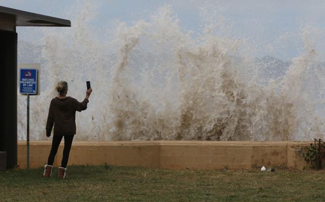 Bystander photographs large waves hitting walls at Haleiwa Beach Park.
