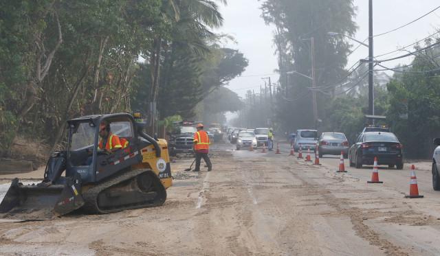 Crews clean up sand and debris along Kamehameha Highway near Sunset Beach, North Shore.