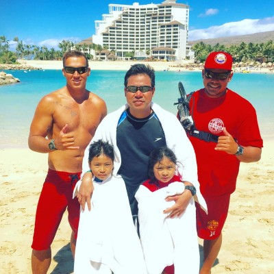 Lifeguards stand with a family they rescued March 9 on the west side of Oahu. The family was swept out to sea on kayaks during a windy day.