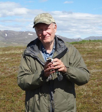 "Montana ecologist Oscar ""Wally"" Johnson with a Pacific golden plover."