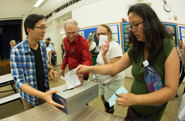 Hawaii Democratic Caucus voters drop their ballots in a shoebox at Stevenson Middle School in Makiki.
