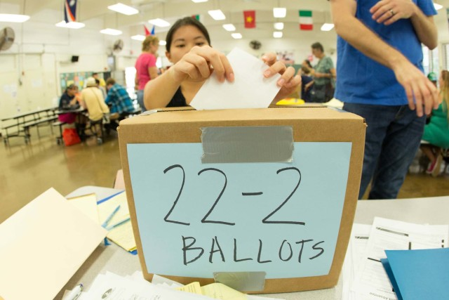 A young voter drops her ballot into a cardboard box at Jefferson Elementary School during Saturday's Democratic caucus.