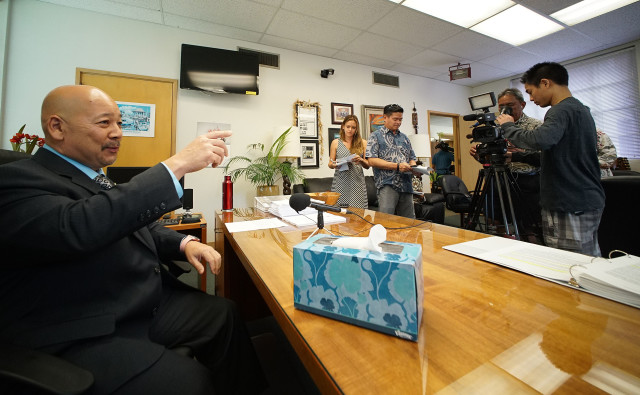 City Council Chair Ernie Martin with a box of tissue/kleenex for mayor on the desk during press conference.