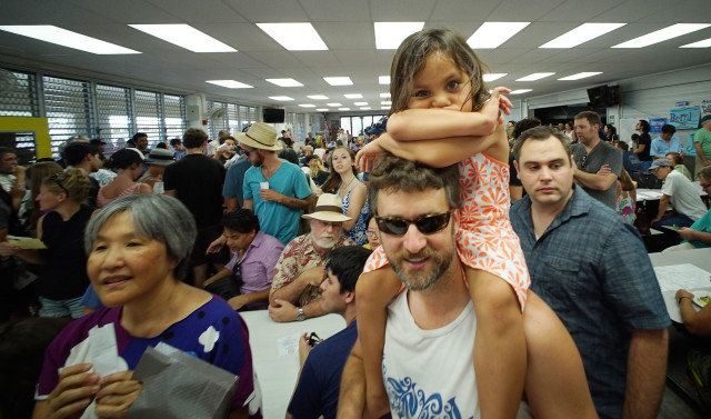 3-year-old Beatrix Puakala Oliver seated on her dad Tom Oliver at District 23, Manoa Elementary School cafeteria. 26 march 2016.