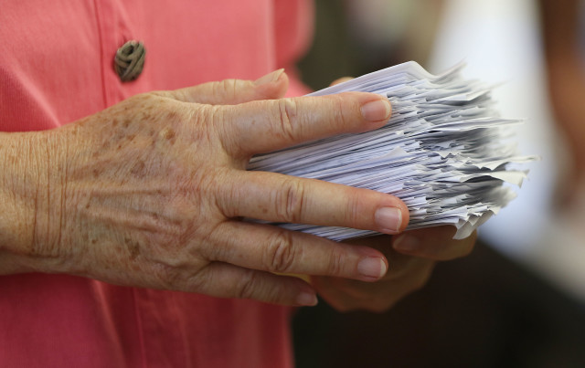 Honolulu City Council Member Ann Kobayashi holds folded secret ballots at Manoa Elementary School's cafeteria as she asked people to fold their ballots. 26 march 2016.