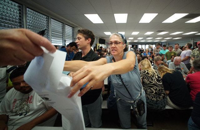 Volunteer Gayle Fox collects ballots at District 23 Manoa Elementary School cafeteria. 26 march 2016.