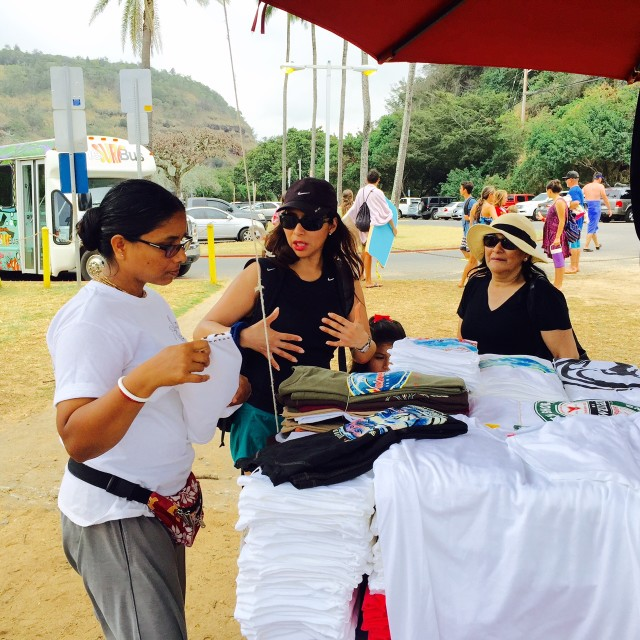 Vendor Madhumala Biswas, left, with customers at Waimea Bay Beach Park.