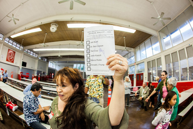 A polling precinct worker at Kalani High School on Oahu shows a ballot.