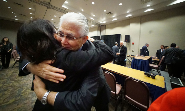 HECO President Alan Oshima embraces after last day of Public Utility Commission hearings at Neal Blaisdell. Hugs weren't uncommon in this PUC hearings.