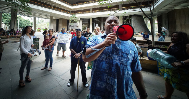 Hauula resident Josh Noga uses a bullhorn to get the attention of senators regarding HB2501 forcing lawmakers into majority caucus room because of the noise. 12 april 2016.