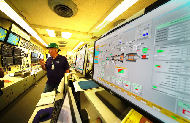 HEI HECO Superintendent of Waiau, William Evans stands in 7/8 control room. HEI HECO Waiau power plant turbine without building. 14 april 2016