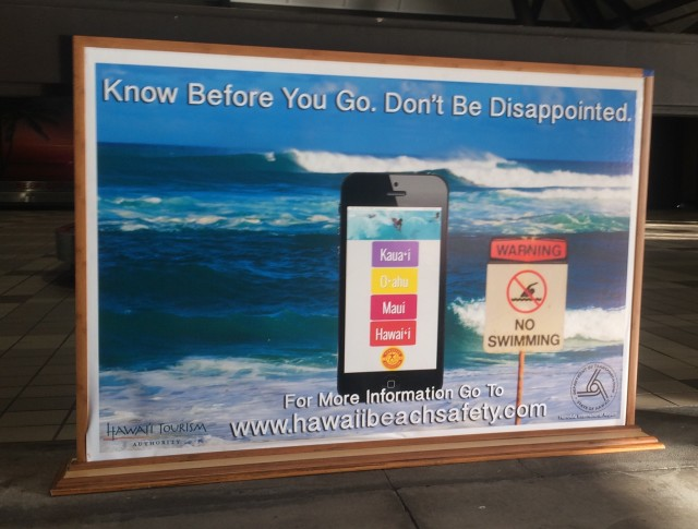 New signs for Hawaii airports designed to encourage visitors to visit a website where they can find real-time information on beach conditions around the state.