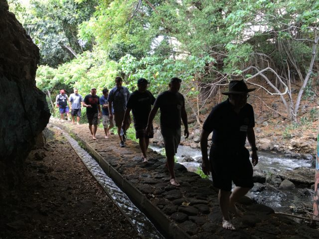 Purple Prize participants walk along the auwai, or irrigation ditch system, that feeds the Kānewai taro fields in Manoa.