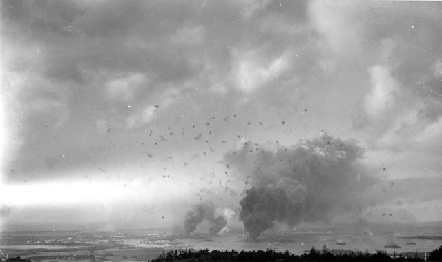 The Japanese raid on Pearl Harbor on Dec. 7, 1941 did surprisingly little damage to HECO facilities including the plant adjacent to the shipyard. This photo looks southwesterly from the hills behind the harbor. The large column of smoke in the lower right center is from the burning USS Arizona..