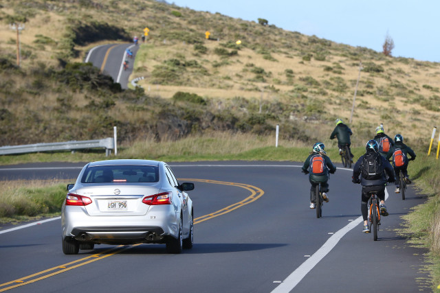 Left, car attempts to pass in a turn to avoid cyclists riding down Haleakala, Maui. 9 july 2016
