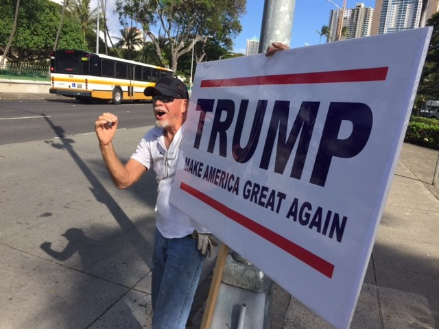 A Trump supporter waves his sign at passing traffic in Honolulu.