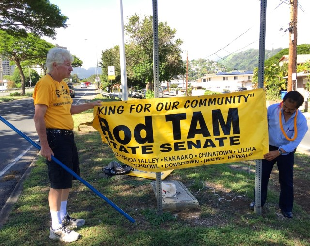 Rod Tam and campaign volunteer Bob Brennan prepare for a sign-waving session recently in Honolulu.