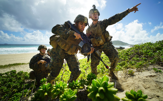 US Marines storm Pyramid Rock Beach Marine Corps Base Hawaii after landing on beach via Amphibious Assault Vehicles in RIMPAC exercises. Kaneohe Hawaii. 30 july 2016