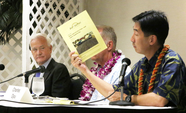 Mayoral candidate Charles Djou holds a copy of a Star Advertiser article as Mayor Kirk Caldwell looks on during Rotary Club mayoral forum held at the Japanese Culture Center of Hawaii. 26 july 2016