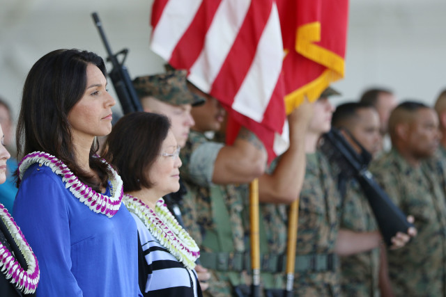 Senator Mazie Hirono and Congresswoman Tulsi Gabbard stand as the colors are retired during ceremonies opening a new MV22 Osprey hangar at Marine Corps Base Hawaii. 19 july 2016