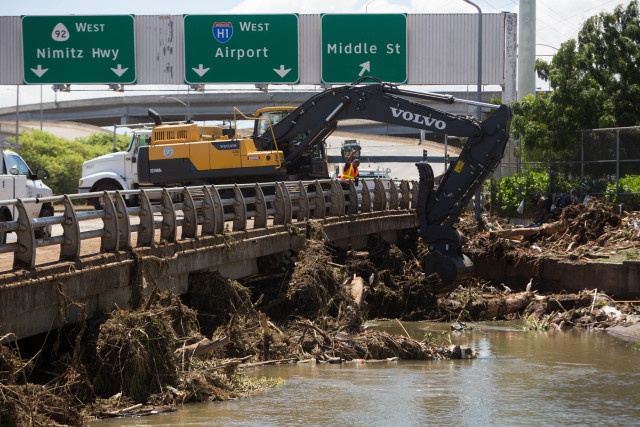 Clean up crews remove debris on the Kalihi River at Kamehameha Highway and Middle Street after Tropical Storm Darby.