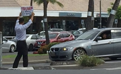 A lone supporter of presidential candidate Donald Trump entertains motorists in Hawaii Kai.