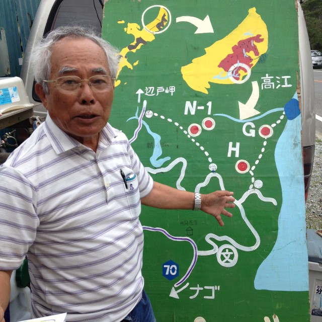 Okinawan naturalist Yoshiyasu Iha stands before a hand-painted map showing where new U.S. military helipads are being built.