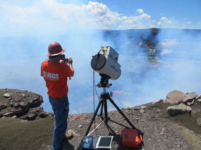 A USGS Hawaiian Volcano Observatory geochemist measuring gases released from Kilauea with a spectrometer.