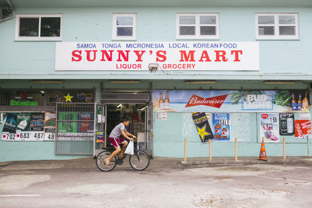 Boy rides away with his purchase from Sunny's Mart in Kalihi.