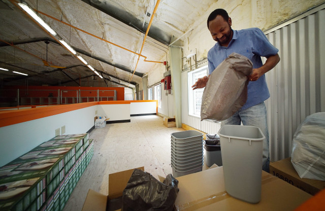 Case Manager Roddy Marengo gets trash containers ready before residents start moving into the building tomorrow. Maximum 50 people can live in this shelter. 27 sept 2016