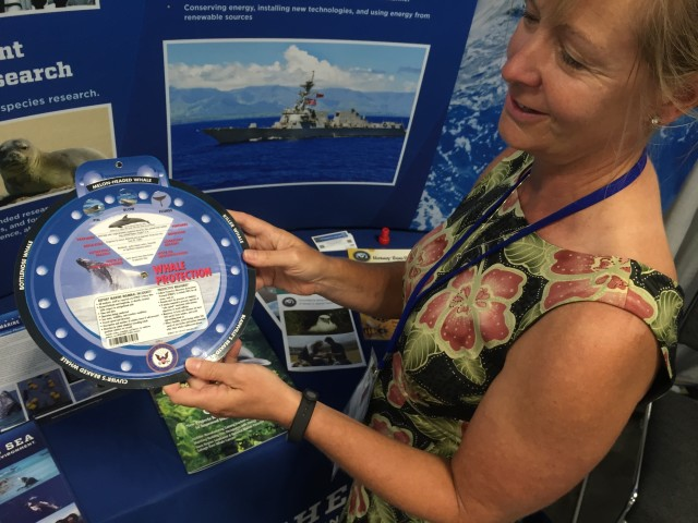 "A representative of the Navy demonstrates a ""whale wheel"" to identify different types of the marine mammals."