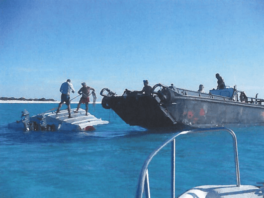 Crew members work to right the 33-foot landing craft that capsized.