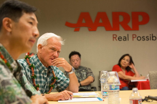Charles DJou and Kirk Caldwell listen to questions over speaker phone during AARP Hawaii's tele-town hall debate.