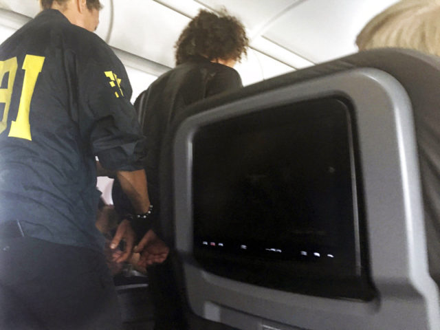 FILE- In this file photo provided by Donna Basden, a man is escorted off an American Airlines flight after it landed in Honolulu, Friday, May 19, 2017. Court records say the man who caused a disturbance on a flight from Los Angeles to Honolulu had no luggage other than a laptop and needed a wheelchair to board the plane because he appeared to be under the influence of drugs or alcohol.(Donna Basden via AP, File)