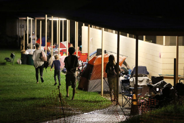 People arrive after 5am to see a formed line of tents and umbrellas at 5am saturday after staying over on beach chairs under tents in lines waiting to register their kids into summer fun programs at Manoa Recreation Center. 13 may 2017